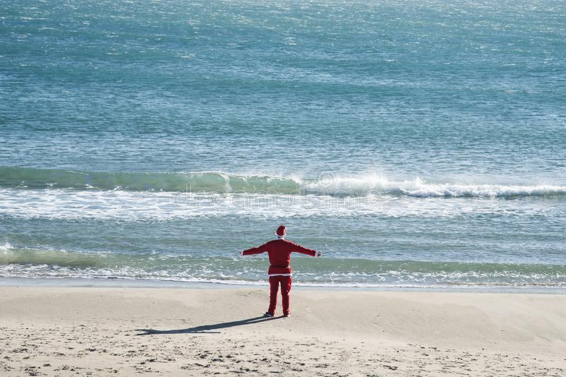 Man in a santa suit standing on the beach. Young man wearing a santa suit, seen from behind, standing on the beach facing the ocean, with his arms outstretched royalty free stock photos