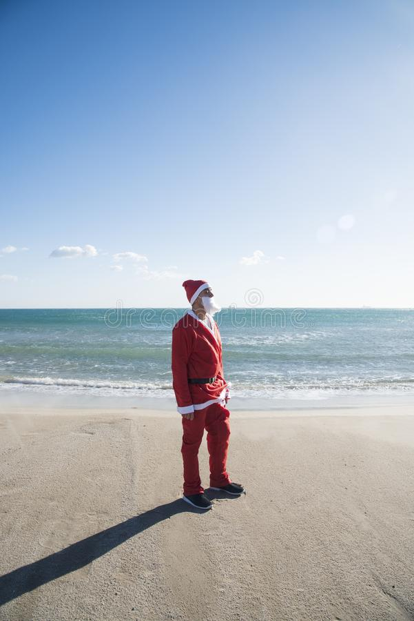 Santa claus on the beach. Young man wearing a santa suit standing on the beach facing the sun, with the ocean in the background royalty free stock photo