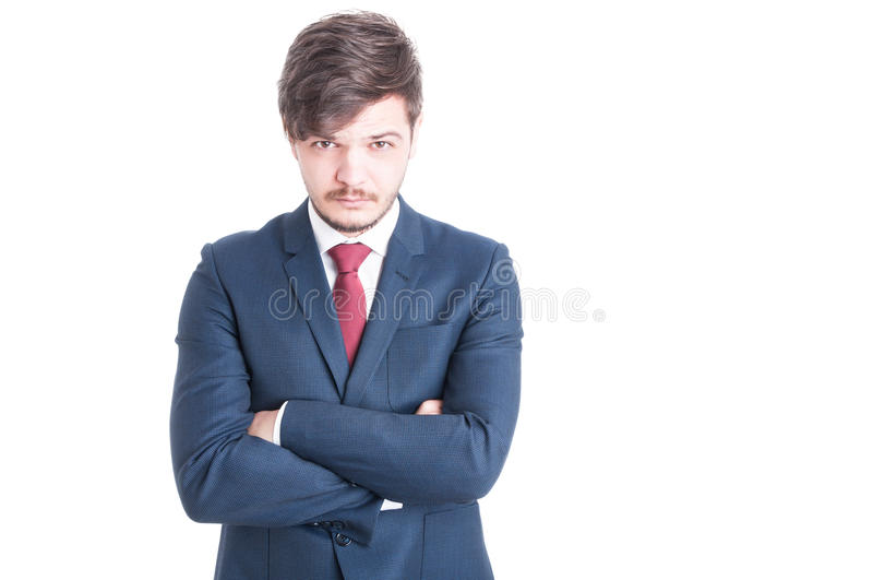 Young man wearing suit posing with arms crossed. And head bowed looking at camera isolated on white background with copy text space royalty free stock photo