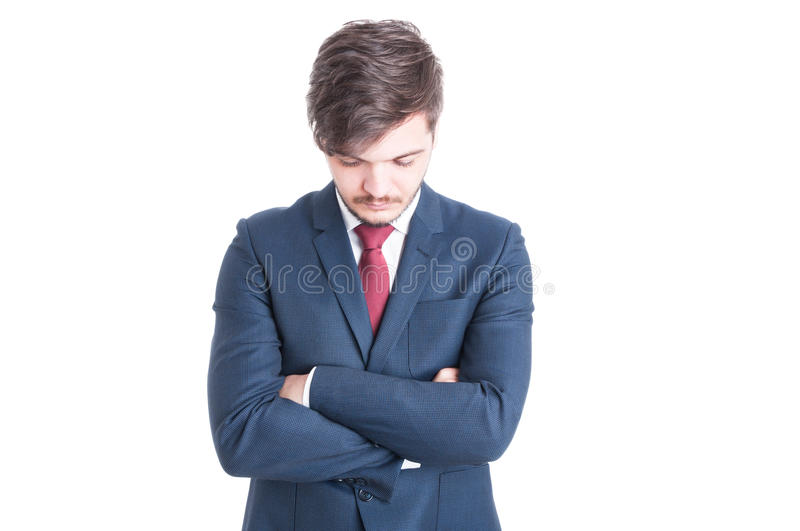 Young man wearing suit standing with arms crossed. And head bowed looking down isolated on white background with copy text space royalty free stock photo