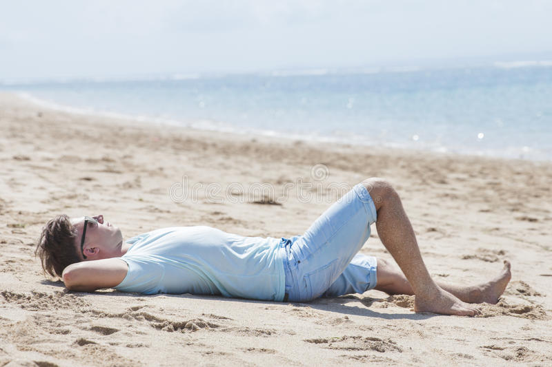 Young man wearing sunglasses while sunbathing at the beach royalty free stock photos