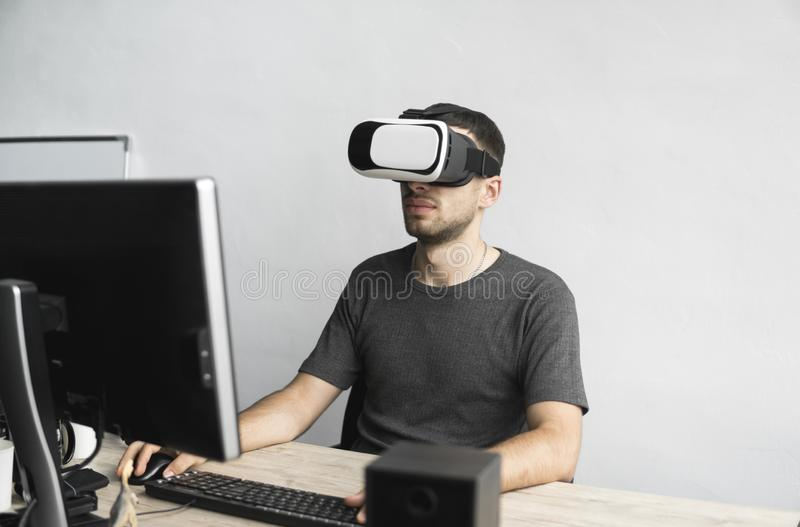Young man wearing virtual reality goggles headset, vr box and sitting in the office against computer monitor. Connection stock photo