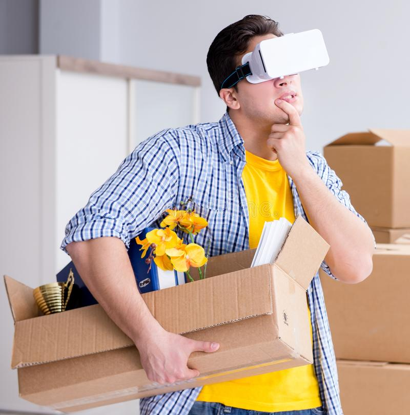 The young man wearing vr glasses moving in new apartment stock image