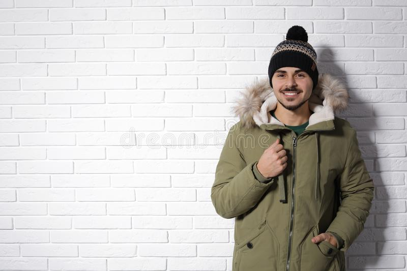 Young man wearing warm clothes against brick wall, space for text. Ready for winter. Vacation stock image
