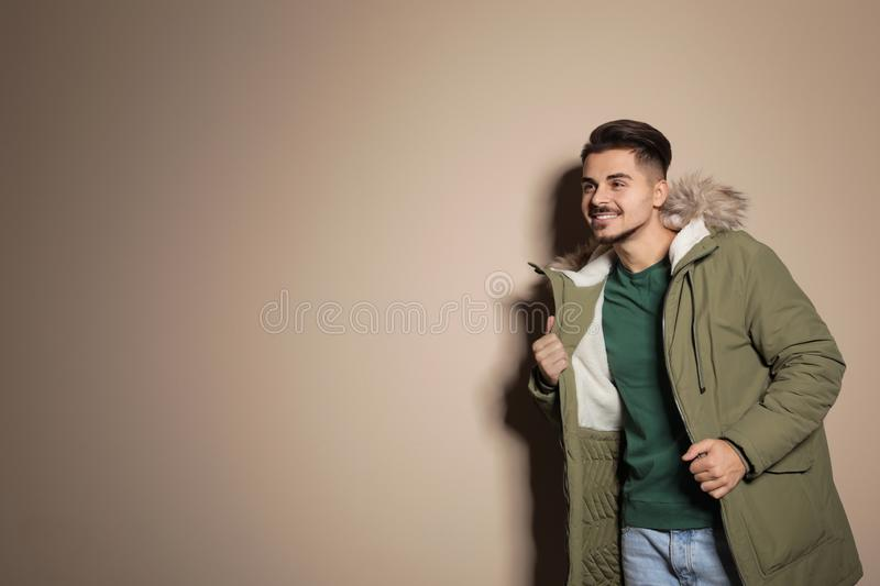 Young man wearing warm clothes on color background, space for text. Ready for winter. Vacation royalty free stock photography