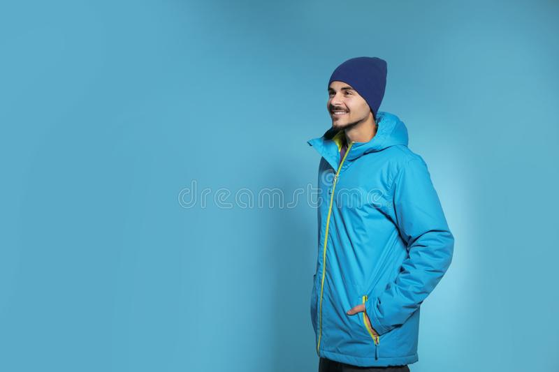 Young man wearing warm clothes on color background, space for text. Ready for winter. Vacation stock image