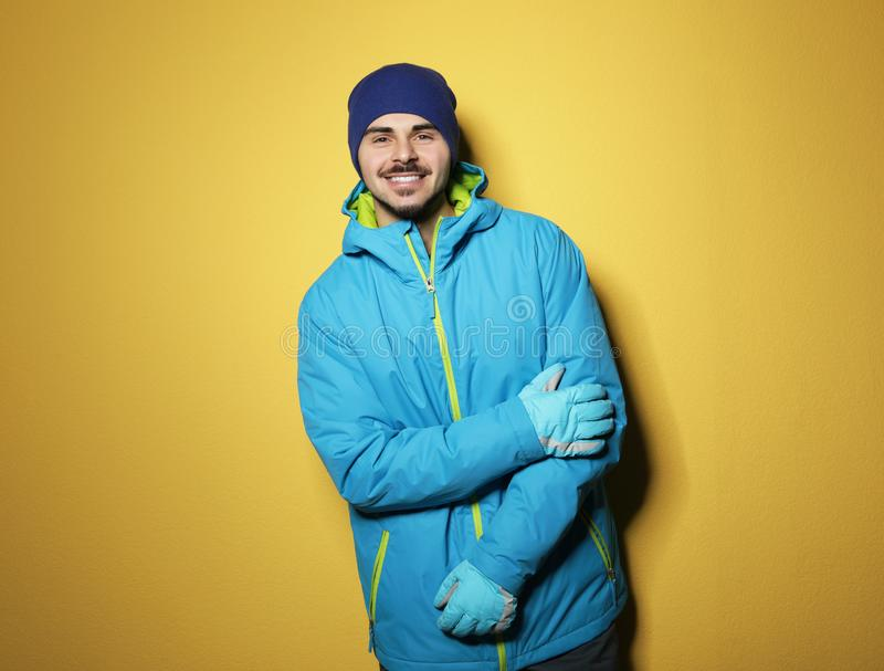 Young man wearing warm clothes on color background, space for text. Ready for winter. Vacation royalty free stock photos