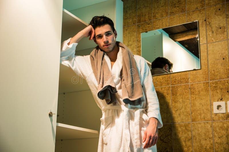 Young man wearing white bathrobe in spa. Handsome young man wearing white bathrobe, standing in spa bath next to closet stock photos