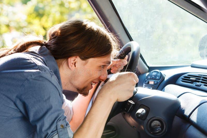 Man in car fooling around. Young man wearing white shirt having long hair, driving car with face close to steering wheel, having fun royalty free stock photo