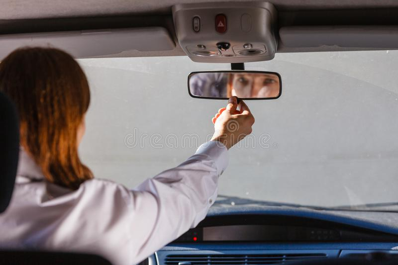 Man in car looking at mirror inside. Young man wearing white shirt having long hair, driving car setting mirror inside to see better whats behind auto royalty free stock image