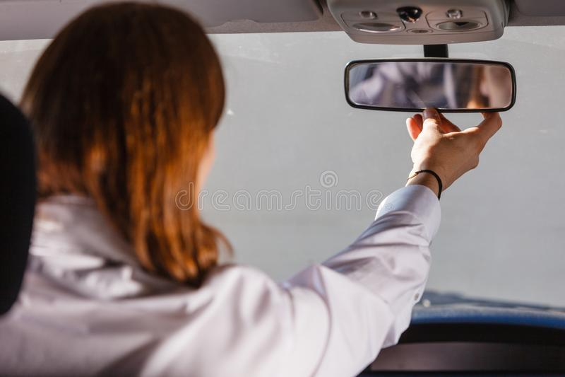 Man in car looking at mirror inside stock photography