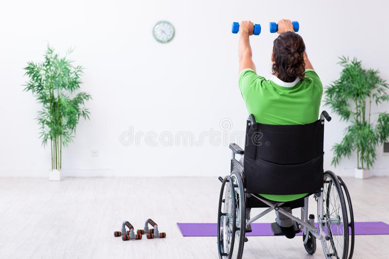 Young man in wheel-chair doing exercises indoors. The young man in wheel-chair doing exercises indoors stock photography