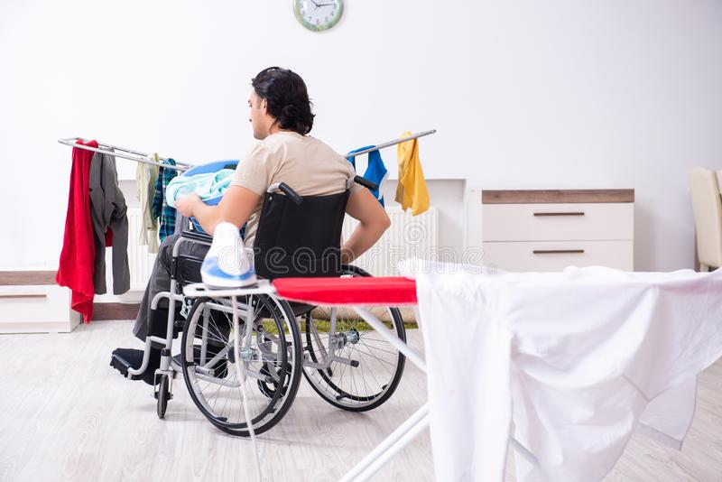 Young man in wheel-chair doing ironing at home. The young man in wheel-chair doing ironing at home royalty free stock photos