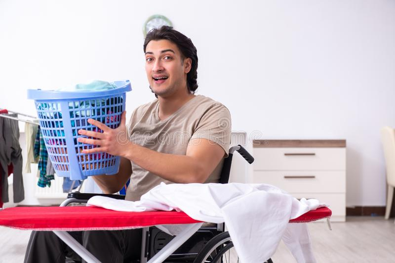 The young man in wheel-chair doing ironing at home royalty free stock photography