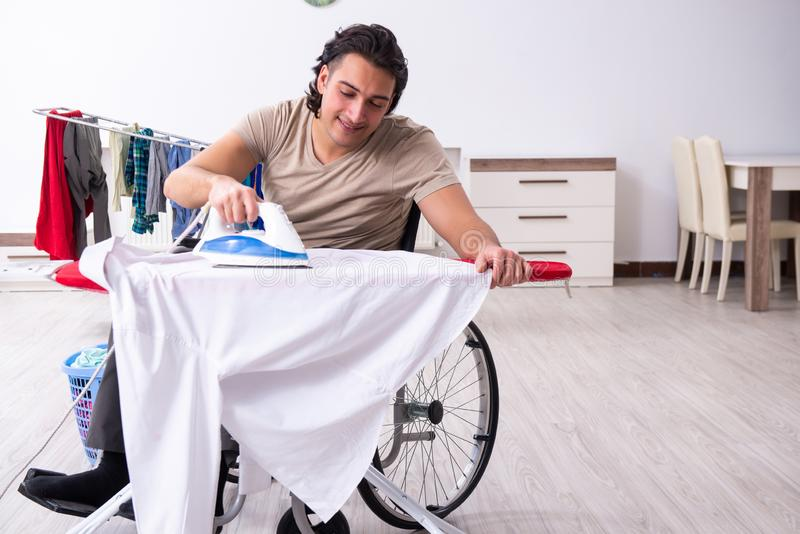 Young man in wheel-chair doing ironing at home. The young man in wheel-chair doing ironing at home stock photos