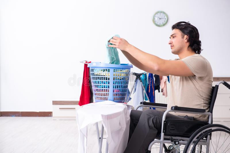Young man in wheel-chair doing ironing at home. The young man in wheel-chair doing ironing at home royalty free stock photography