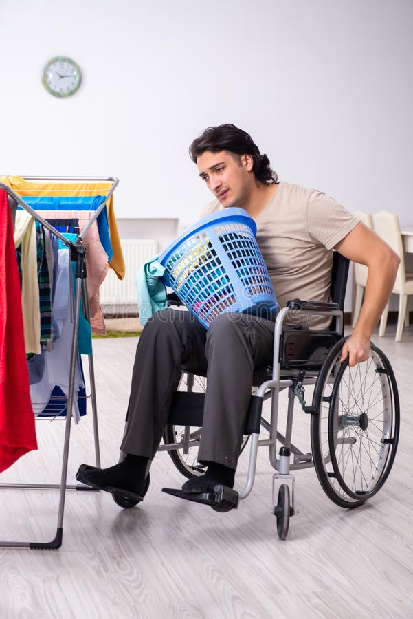 Young man in wheel-chair doing ironing at home. The young man in wheel-chair doing ironing at home stock photo
