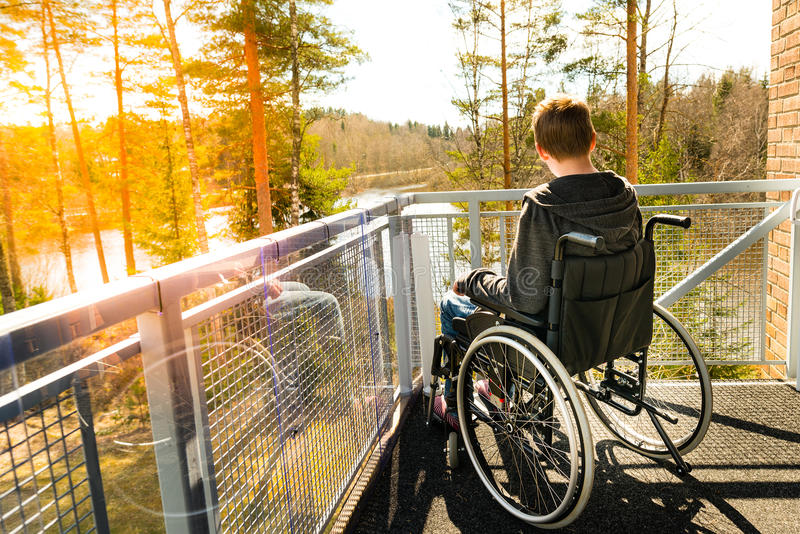 Young man in a wheelchair on a balcony looking at the nature in stock photo