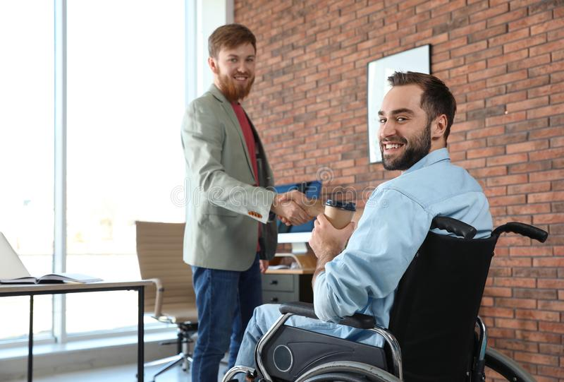 Young man in wheelchair with colleague stock photo