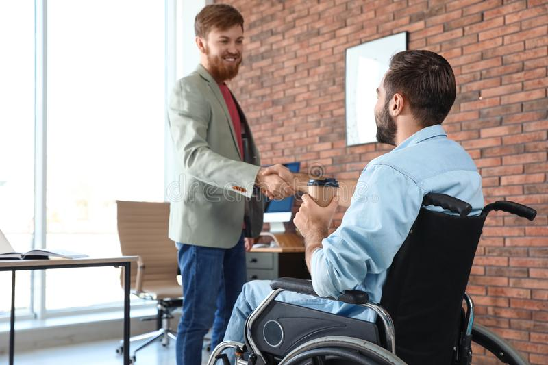 Young man in wheelchair with colleague. Young men in wheelchair with colleague at office stock photo