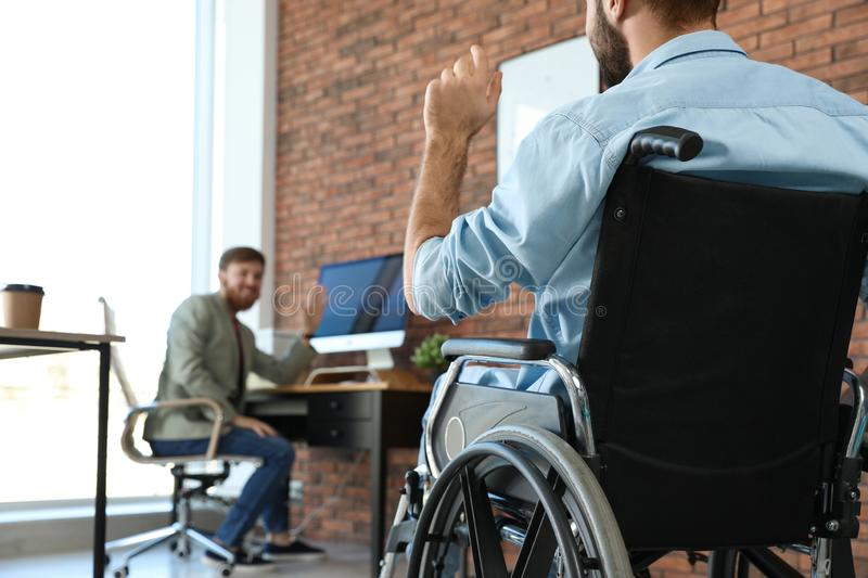Young man in wheelchair with colleague at office stock photos