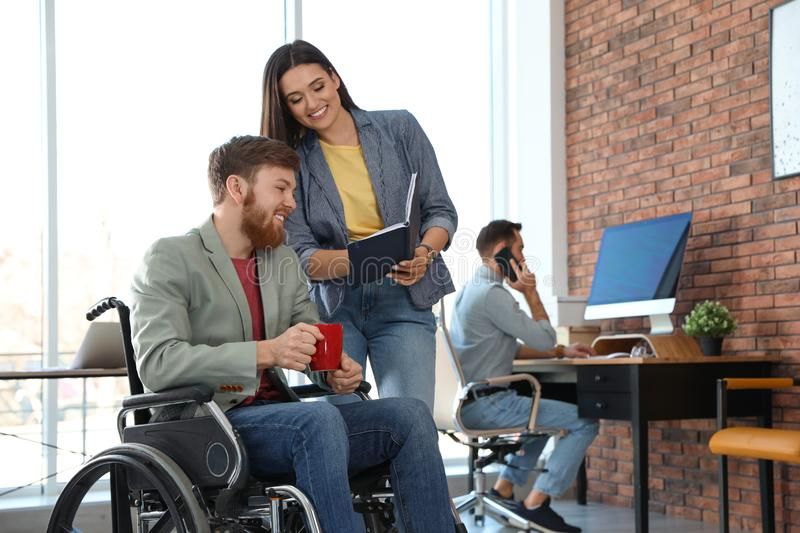 Young man in wheelchair with colleagues stock photography