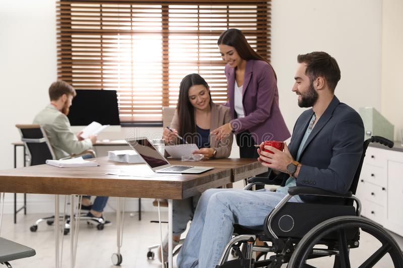 Young man in wheelchair with colleagues. Young men in wheelchair with colleagues at workplace royalty free stock photos