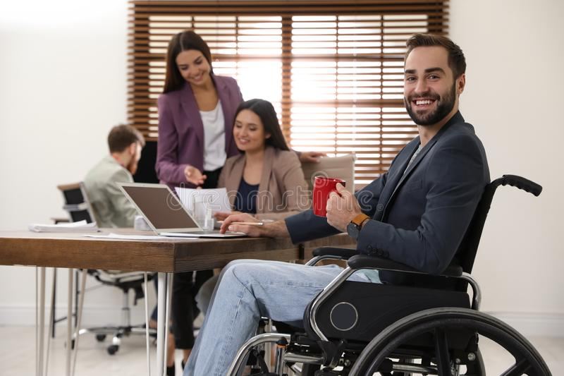 Young man in wheelchair with colleagues royalty free stock images