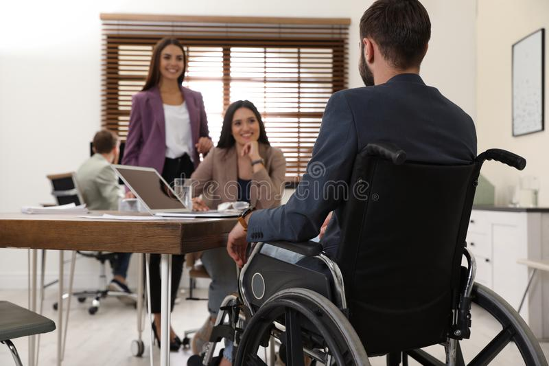 Young man in wheelchair with colleagues. Young men in wheelchair with colleagues at workplace stock image