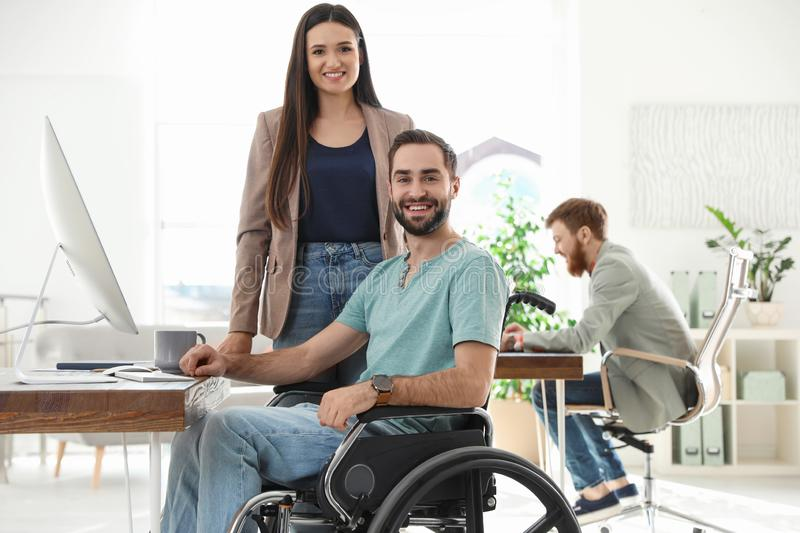 Young man in wheelchair with colleagues. Young men in wheelchair with colleagues at workplace royalty free stock image