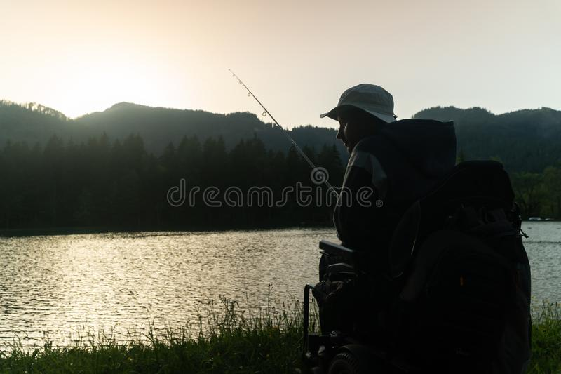 Young man in a wheelchair fishing at the beautiful lake in sunset, dawn stock image