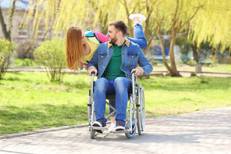 Young man in wheelchair and joyful woman royalty free stock photos