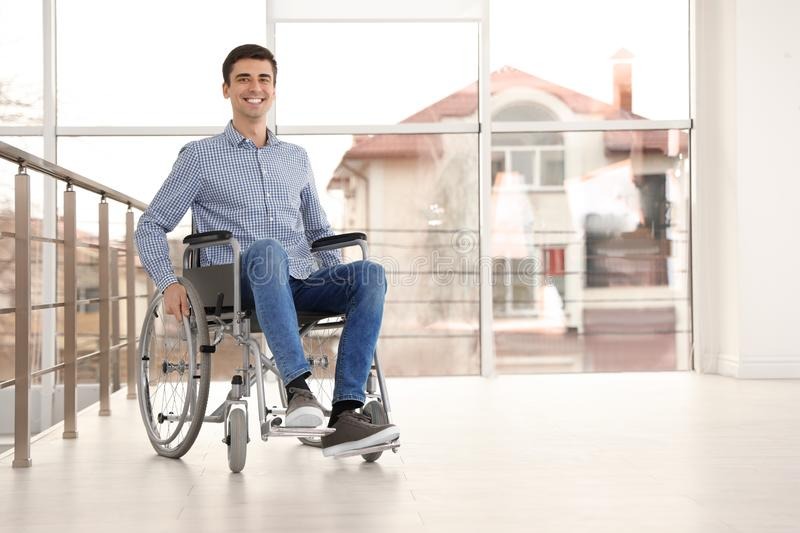 Young man in wheelchair near window indoors stock images