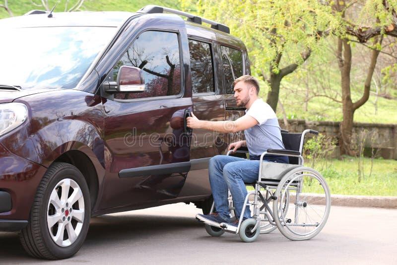 Young man in wheelchair opening door of his van stock image