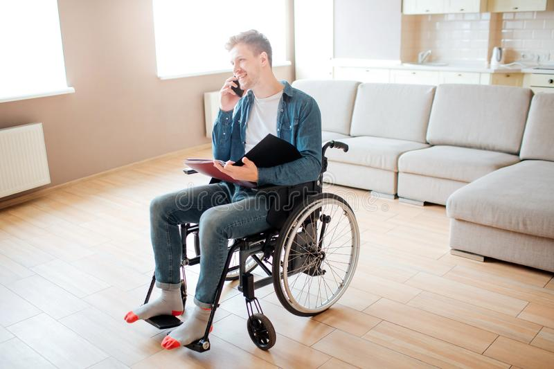 Young man in wheelchair. Person with special needs. Disability. Student sitting and talking on phone. Holding opened stock photos