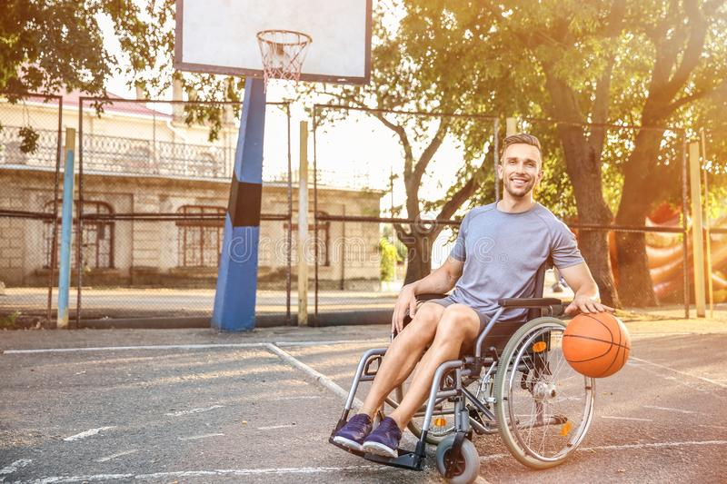 Young man in wheelchair playing basketball outdoors stock image