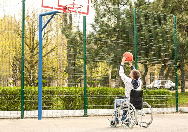 Young man in wheelchair playing basketball on  ground royalty free stock photography