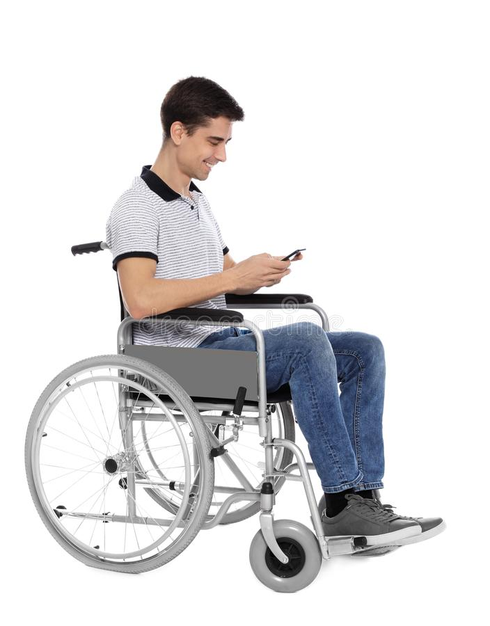 Young man in wheelchair using mobile phone isolated royalty free stock photo