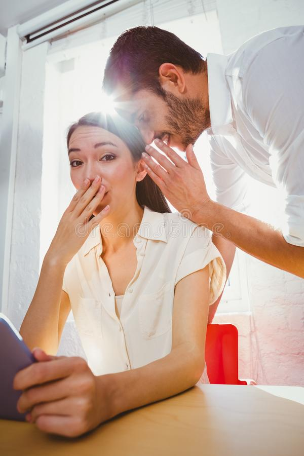 Man whispering secret into friends ear royalty free stock photos