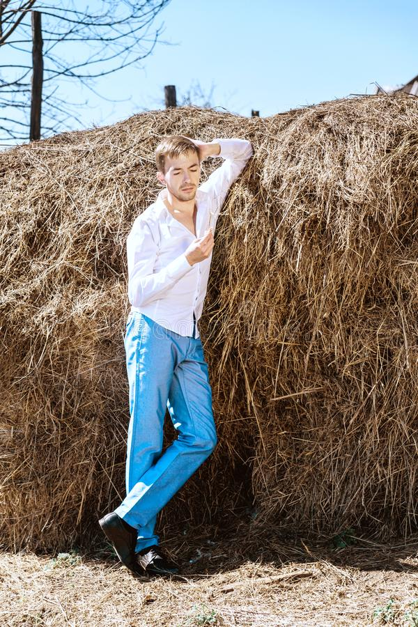 A young man in a white shirt and blue pants leaned against a haystack stock photo
