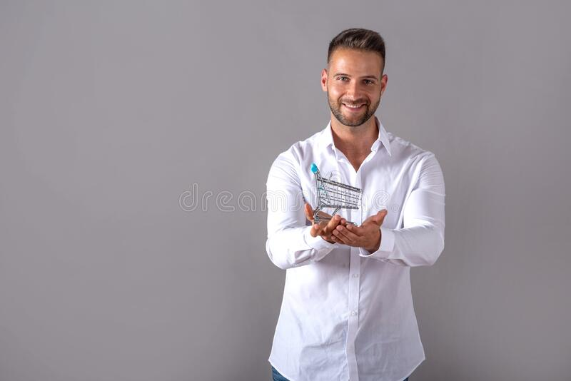 A man in a white shirt holding a mini shopping cart royalty free stock photography