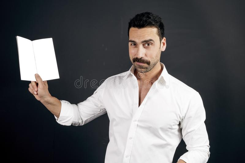 Young man in white shirt reading a booklet. Young handsome man with beard and moustache showing a brochure against black background, studio portrait stock photos