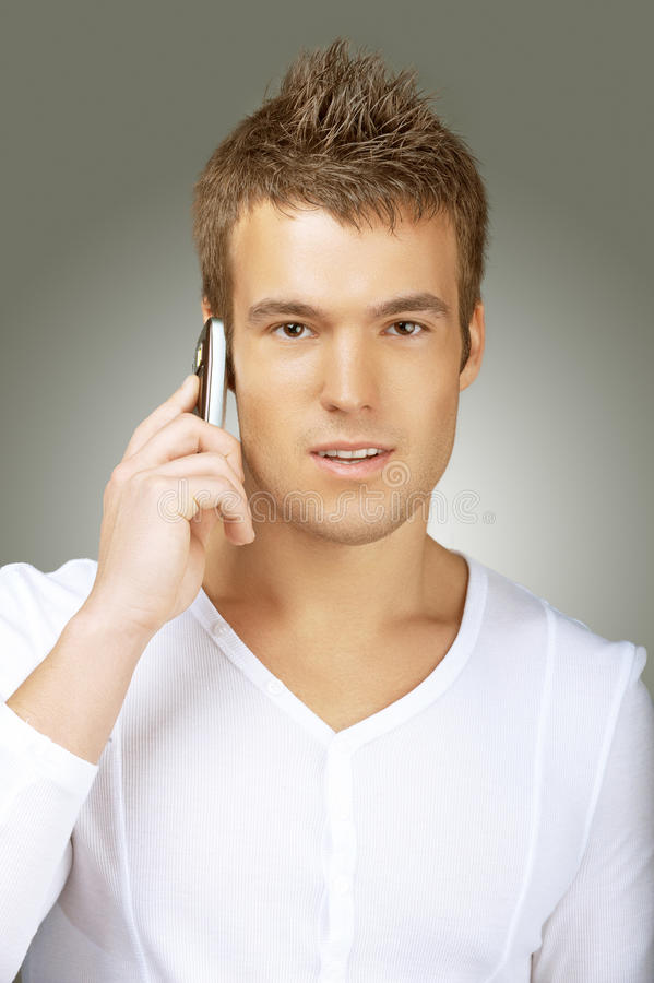Young man in white shirt talking on cell phone stock photos