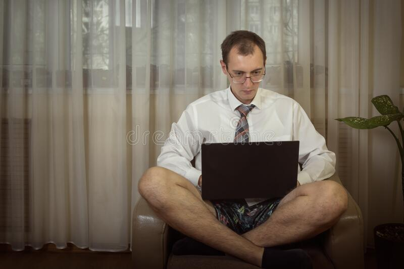 Young man in a white shirt with a tie and underwear works at a computer at home. Toned. Copy space royalty free stock images