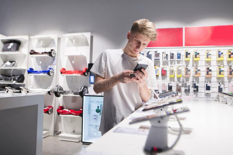 Young man in a white T-shirt chooses a smartphone in the electronics store. A student buys a phone in the store stock photos