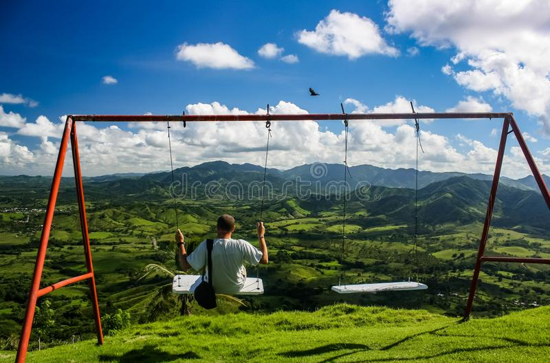A young man in white T-shirt swinging on a swing stock photo