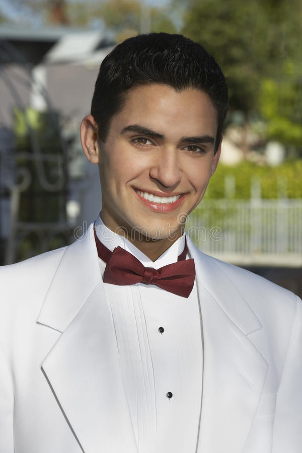 Young Man In White Tuxedo At Quinceanera. Portrait of a young handsome Hispanic man in white tuxedo at Quinceanera stock image
