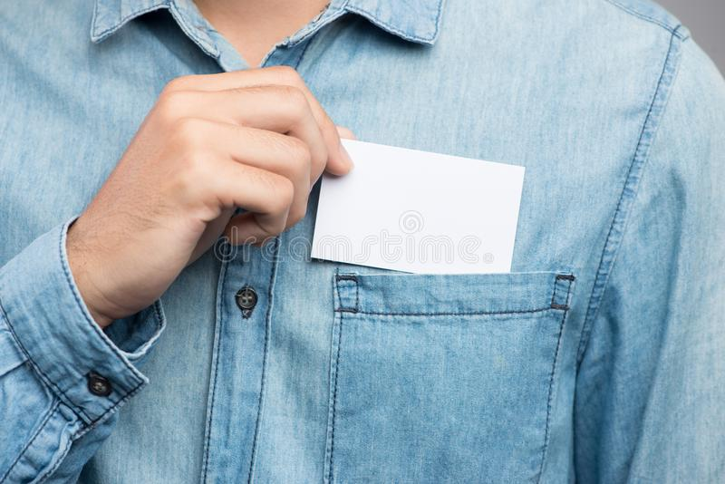Young man who takes out blank business card from the pocket of h. Is shirt stock image