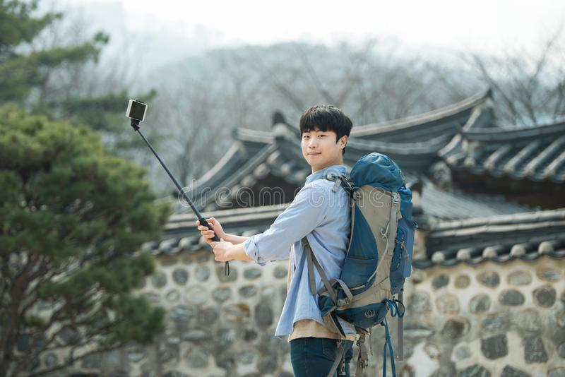 Young man who travels to Korea is taking pictures using his smartphone. stock photography