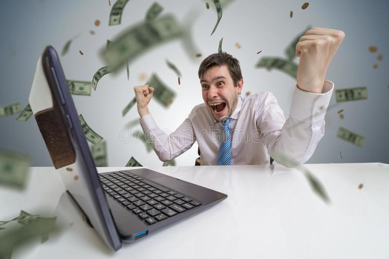 Young man wins a lottery online. Money are falling from above. Online betting concept royalty free stock images